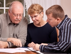 picture of seniors working on documents with a man